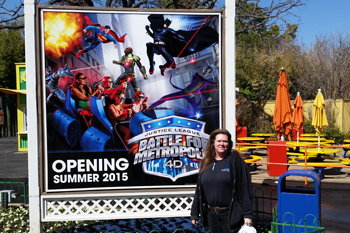 Field Technician Lisa Hasen in front of Opening Soon sign for Interactive dark ride Justice League: Battle For Metropolis 4D at Six Flags Theme Park, U.S.A.