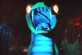 Colorful LED accent lighting at night of a large snake statue at Swampy Jack's Wongo Adventure image 1